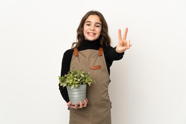 Menina segurando uma planta isolada na parede branca, sorrindo e mostrando o sinal da vitória