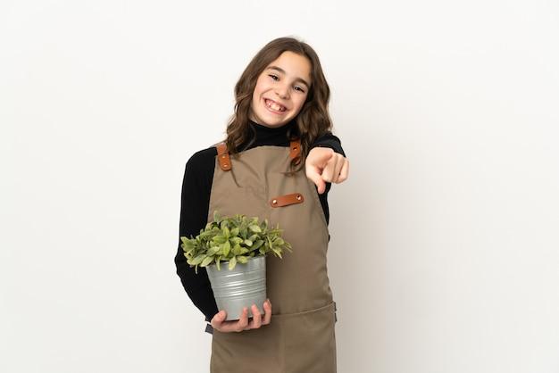 Menina segurando uma planta isolada no fundo branco apontando para a frente com uma expressão feliz