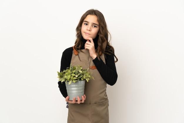 Menina segurando uma planta isolada no fundo branco pensando