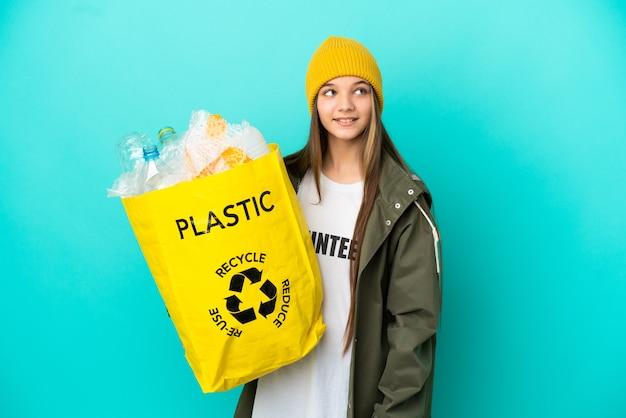 Menina segurando uma sacola cheia de garrafas de plástico para reciclar sobre um fundo azul isolado, tendo uma ideia enquanto olha para cima