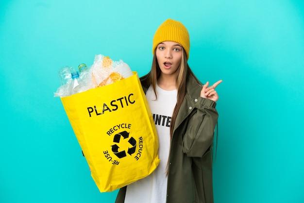 Menina segurando uma sacola cheia de garrafas de plástico para reciclar sobre uma superfície azul isolada, tendo uma ideia apontando o dedo para cima