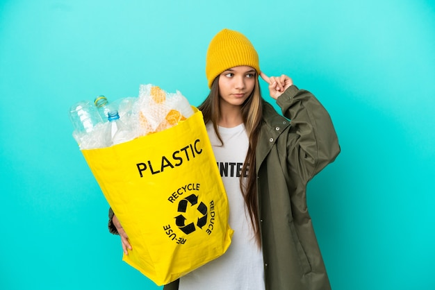 Menina segurando uma sacola cheia de garrafas plásticas para reciclar sobre fundo azul isolado, tendo dúvidas e pensando
