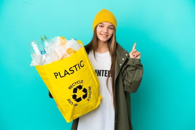 Menina segurando uma sacola cheia de garrafas plásticas para reciclar sobre um fundo azul isolado apontando uma ótima ideia