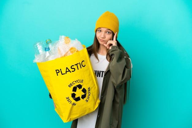 Menina segurando uma sacola cheia de garrafas plásticas para reciclar sobre um fundo azul isolado pensando em uma ideia