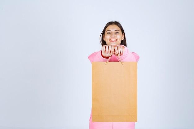 Menina segurando uma sacola de compras de papelão e oferecendo ao cliente.