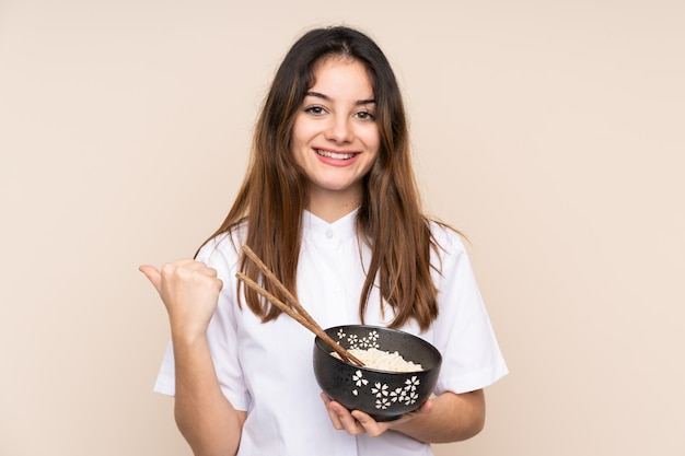Menina, segurando uma tigela cheia de macarrão sobre isolado apontando para o lado para apresentar um produto