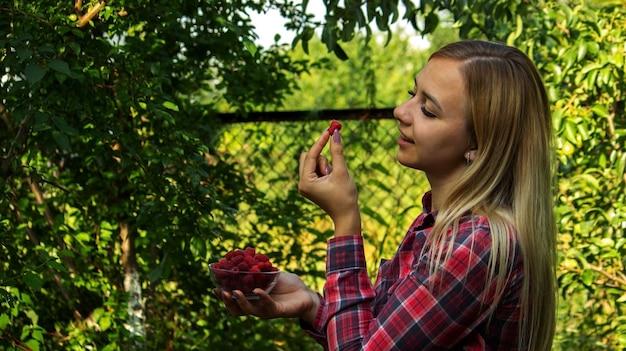 Menina segurando uma tigela com produto orgânico de framboesas maduras na fazenda. foco seletivo
