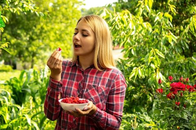 Menina segurando uma tigela com produto orgânico de framboesas maduras na fazenda.