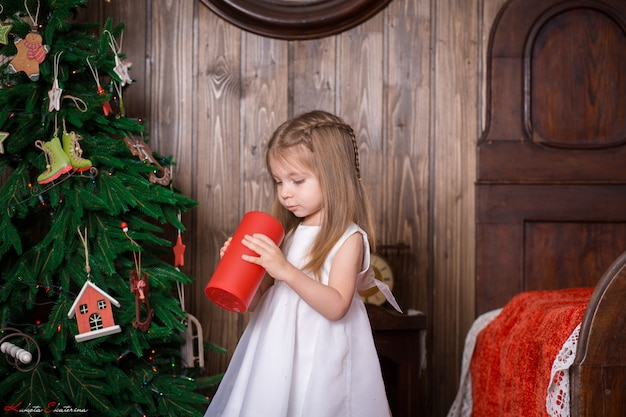 Menina, segurando uma vela vermelha decorativa para decorar um quarto para as férias de natal