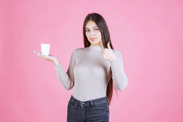 Menina segurando uma xícara de café e mostrando o sinal de polegar