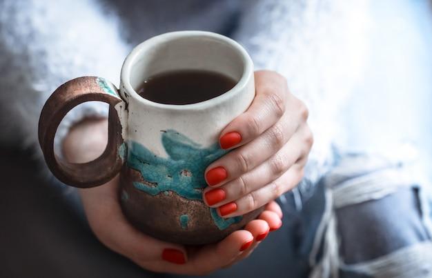Menina segurando uma xícara de chá nas mãos
