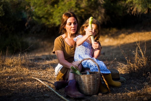 Menina, segurando, vegetal, sentando, em, dela, mother's, colapso, ligado, campo