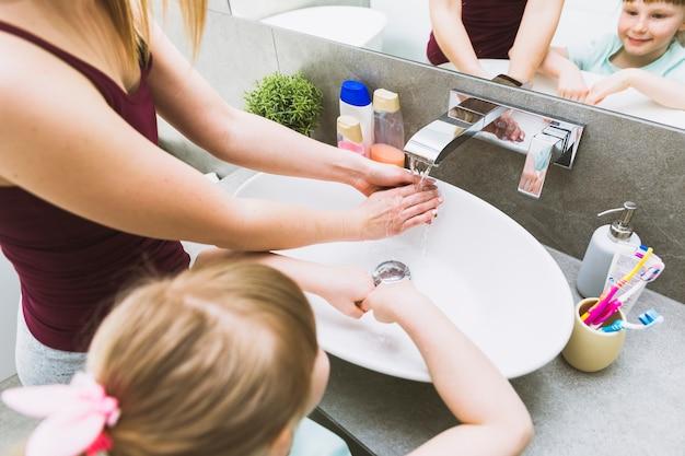Menina sem rosto e mulher lavar as mãos