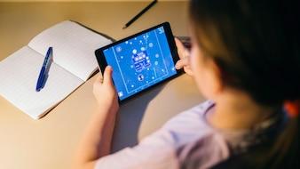 Menina sem rosto jogando jogo de tablet enquanto estudava