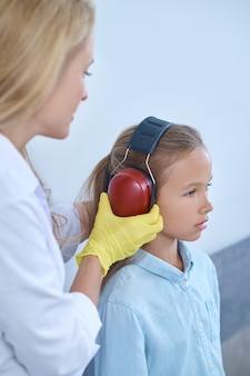 Menina sendo preparada para um teste de audição por um profissional médico