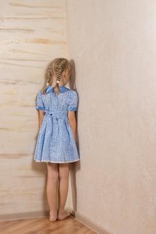Menina sendo punida em pé no canto