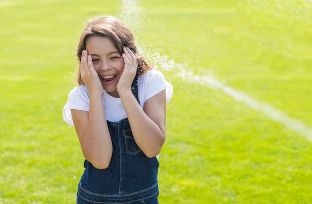 Menina sendo regada com uma pistola de água
