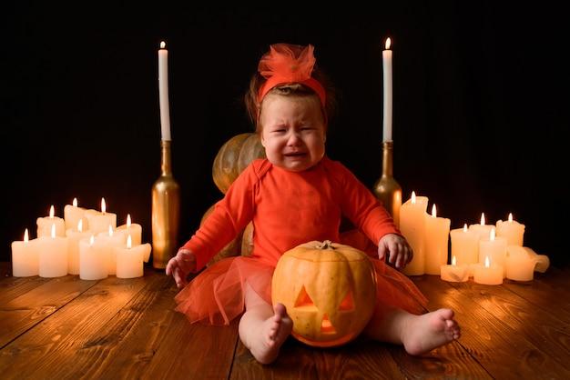Menina senta-se com abóboras jack e velas