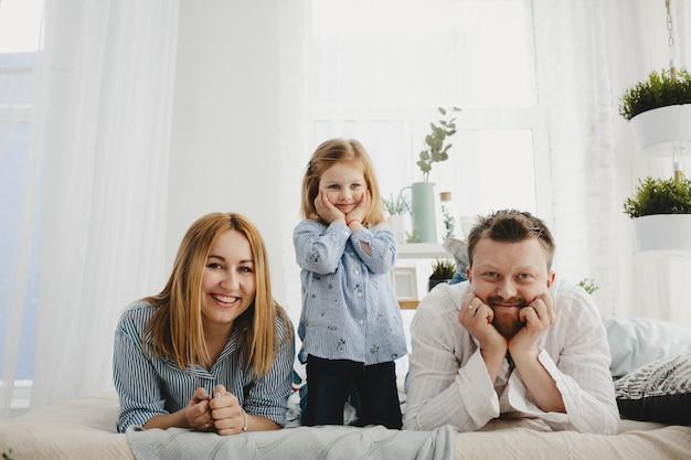 Menina senta-se com os pais em uma cama branca em um quarto brilhante
