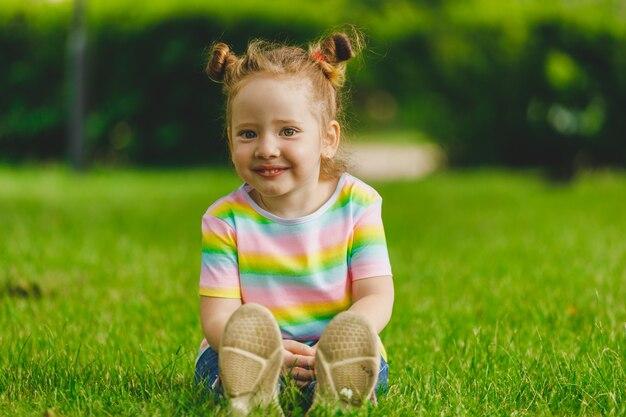 Menina senta-se na grama de verão no parque.