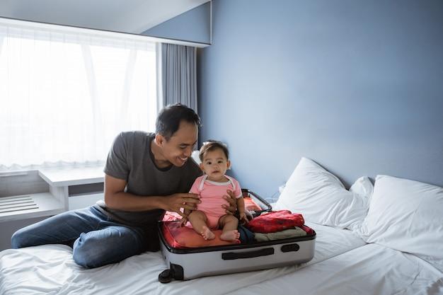 Menina senta-se no colo de pais asiáticos enquanto prepara roupas