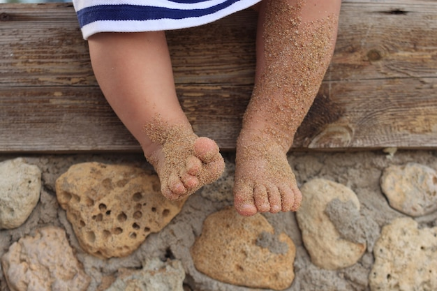 Menina senta-se pesando as pernas de seus filhos na areia