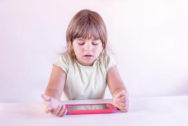Menina sentada à mesa e brincando em um tablet