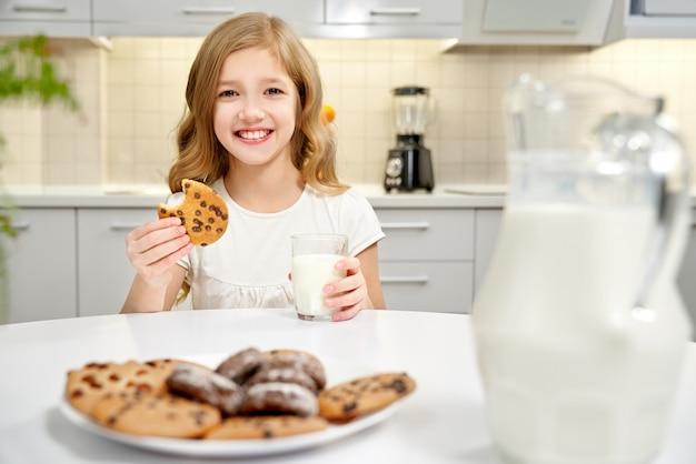 Menina sentada à mesa, segurando o copo de leite e biscoitos.
