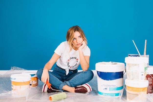 Menina sentada ao lado de materiais de tinta