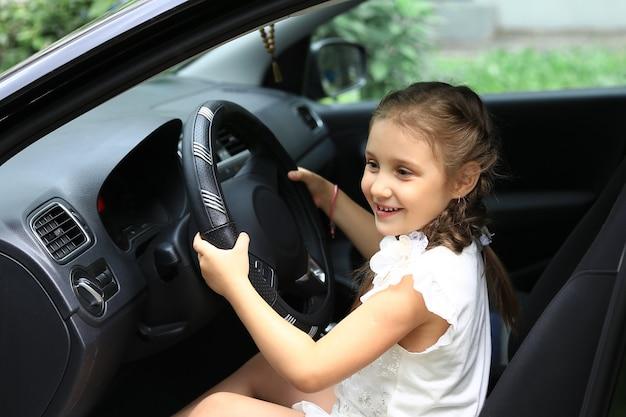 Menina sentada atrás do volante do carro do pai