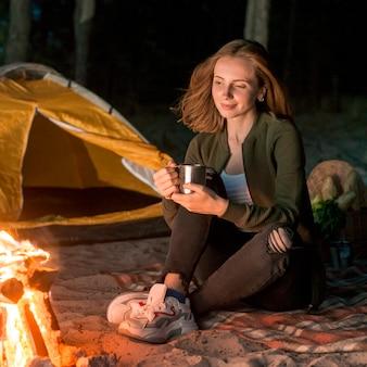 Menina sentada bebendo por uma fogueira