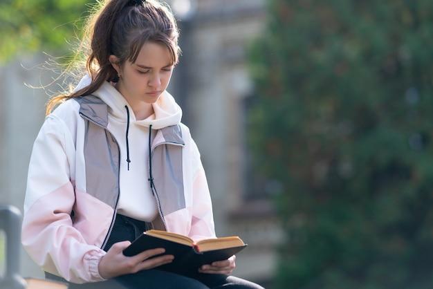 Menina sentada calmamente ao ar livre, lendo um livro