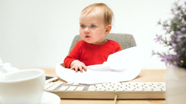 Menina sentada com o teclado do computador moderno ou laptop no estúdio branco.