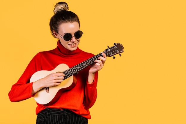 Menina sentada com óculos jogando o ukelele