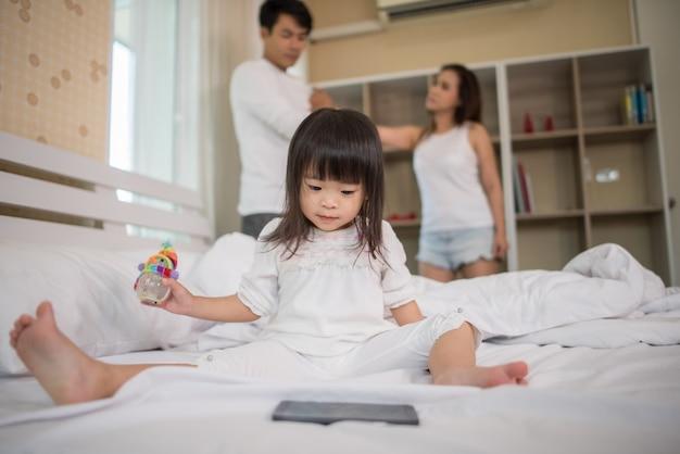 Menina sentada com os pais na cama olhando séria