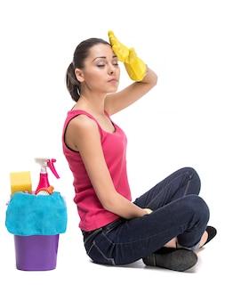 Menina sentada com produtos de limpeza e descansando.