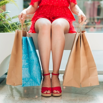 Menina sentada com sacos de compras