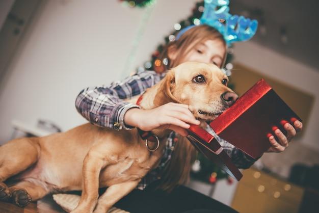Menina sentada com seu cachorro e abrindo o presente de natal
