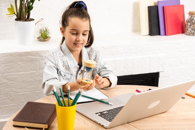 Menina sentada com um laptop na mesa e segurando uma ampulheta