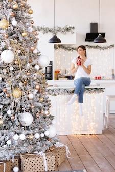 Menina sentada com uma xícara de chocolate quente em uma mesa da cozinha no natal