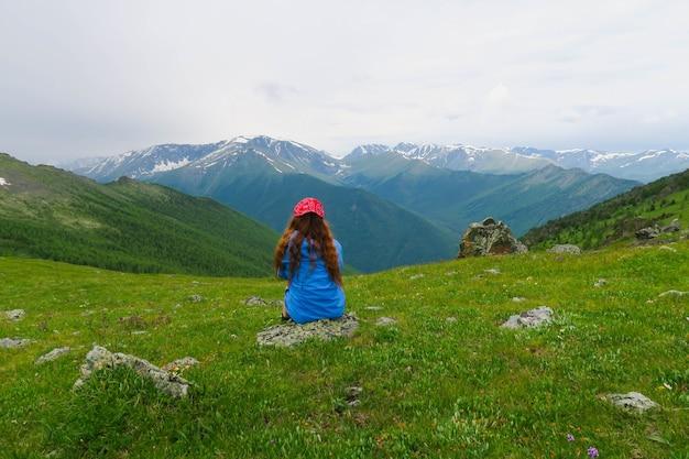 Menina sentada e olhando para as montanhas