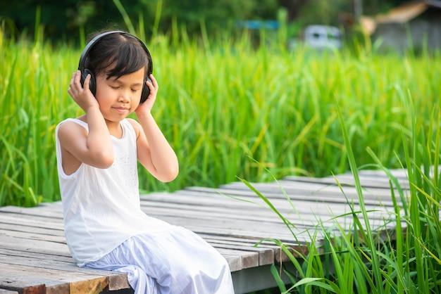 Menina sentada e ouvindo música na ponte de madeira no campo de arroz no pôr do sol