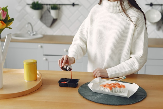 Menina sentada em casa à mesa com um sushi