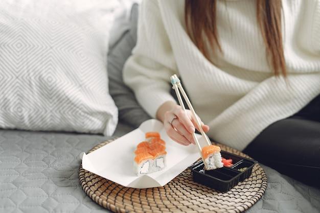Menina sentada em casa em um sofá com um sushi