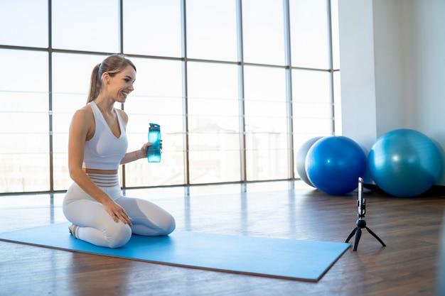 Menina sentada em frente à câmera do telefone e grava exercícios online