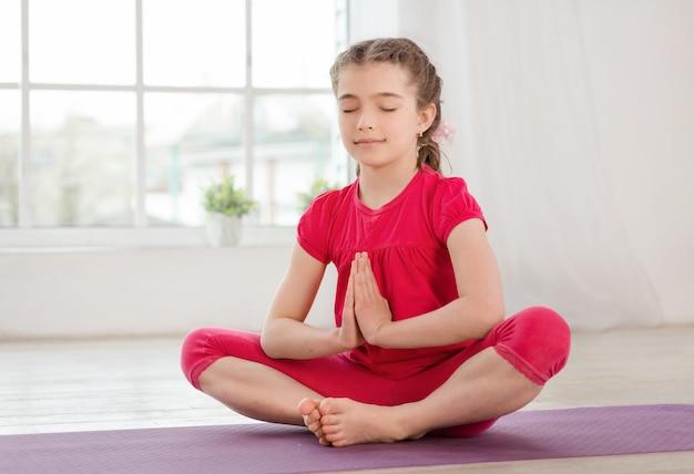 Menina sentada em posição de lótus, com os olhos fechados
