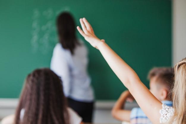 Menina sentada em sala de aula levantando mão