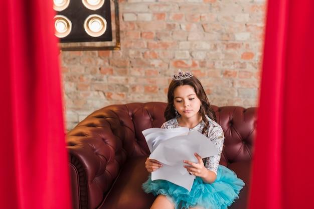 Menina sentada em scripts de leitura nos bastidores