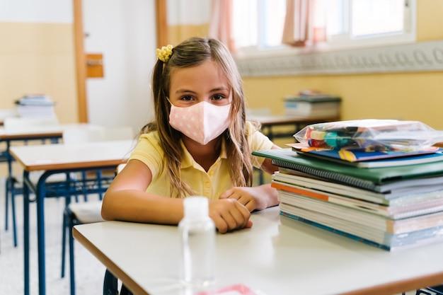 Menina sentada em sua cadeira e mesa na sala de aula usando uma máscara para se proteger durante a terrível pandemia