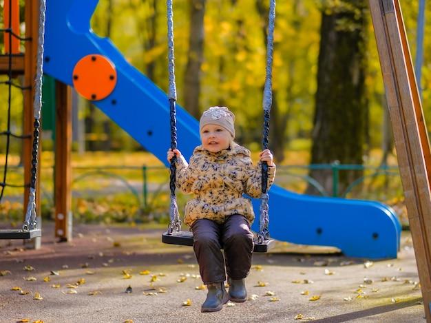 Menina sentada em um balanço em um parquinho em um parque de outono